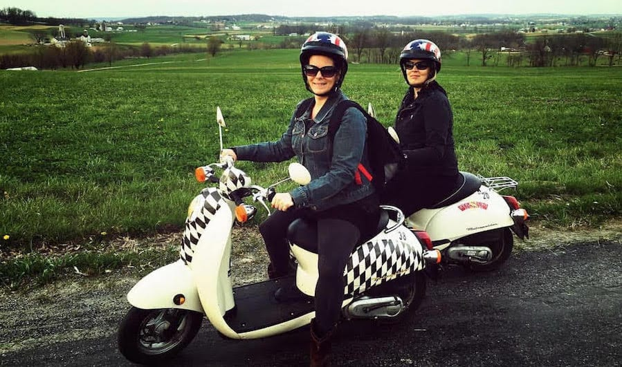 Two riders astride scooters